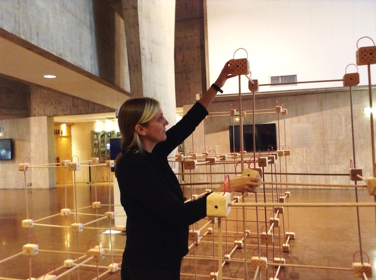 "Photo: Prof. Erin Moore constructs a ""future"" home for bees during UNESCO conference. Credit: A.D. McKenzie 