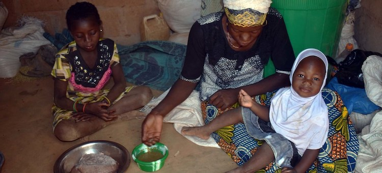 Photo: In Kaya, Burkina Faso, 27-year-old Mariam Sawadogo serves a meal to her family with food from the World Food Programme (WFP). Credit: WFP/Mahamady Ouedraogo.