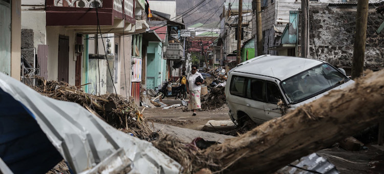 Photo: A woman walks in the street of Roseau, capital of Dominica, which has struggled to overcome the severe impact of two category 5 hurricanes which tore through the region in September 2017. Credit: UNICEF/Moreno Gonzalez