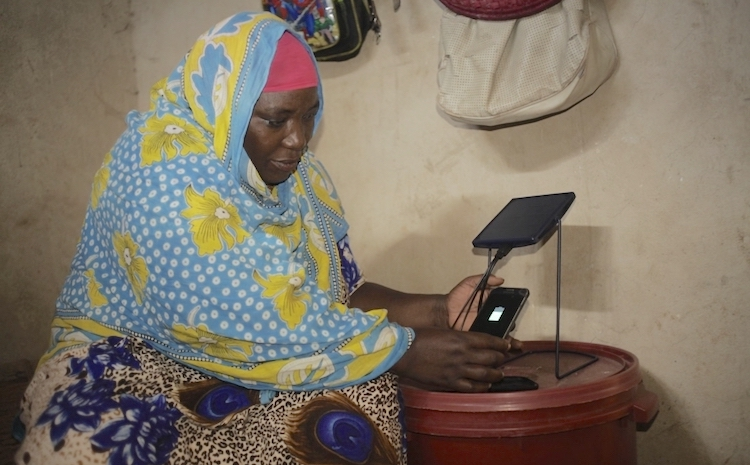 Photo: Mariam Kassim Salum charging her phone on a solar equipment at Kizimkazi village in Zanzibar, Tanzania. Courtesy: Barefoot College